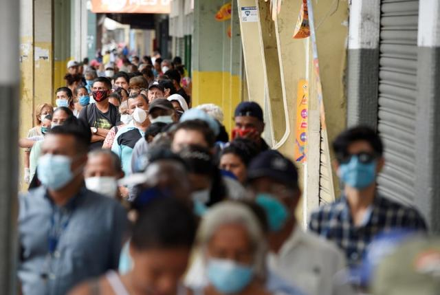 Elderly stand in line to collect their monthly pension before the 4:00 pm - 8:00 am curfew imposed by the government to prevent the spread of the coronavirus disease (COVID-19), in Guayaquil, Ecuador March 20, 2020. REUTERS/Santiago Arcos