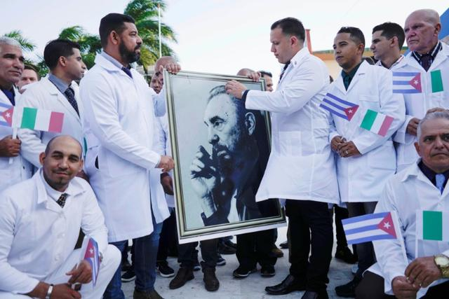 Cuban doctors hold an image of late Cuban President Fidel Castro during a farewell ceremony before departing to Italy to assist, amid concerns about the spread of the coronavirus disease (COVID-19) outbreak, in Havana, Cuba, March 21, 2020. REUTERS/Alexandre Meneghini