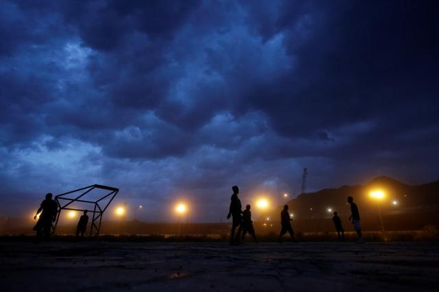 FILE PHOTO: Men play soccer near a section of the U.S.-Mexico border fence as seen from Ciudad Juarez, Mexico July 31, 2017. REUTERS/Jose Luis Gonzalez