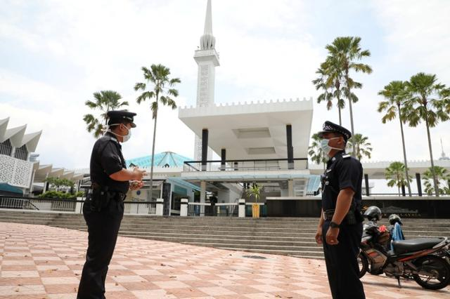 FILE PHOTO: Police officers wearing protective masks stand guard outside National Mosque, after all mosques in the country suspended Friday prayers during the movement control order due to the spread of the coronavirus disease (COVID-19), in Kuala Lumpur, Malaysia March 20, 2020. REUTERS/Lim Huey