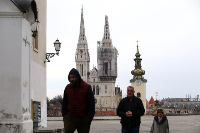 People walk as the cathedral of Zagreb is seen damaged following an earthquake, in Zagreb, Croatia March 22, 2020. REUTERS/Antonio Bronic