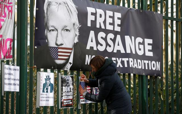 A supporter of WikiLeaks founder Julian Assange posts a sign on the Woolwich Crown Court fence, ahead of a hearing to decide whether Assange should be extradited to the United States, in London, Britain February 25, 2020. REUTERS/Henry Nicholls