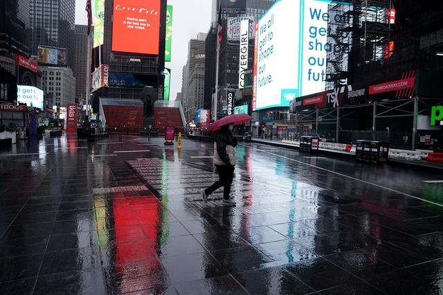 FILE PHOTO: A lone person walks in the rain in a mostly deserted Times Square following the outbreak of Coronavirus disease (COVID-19), in the Manhattan borough of New York City, New York, U.S., March 23, 2020. REUTERS/Carlo Allegri