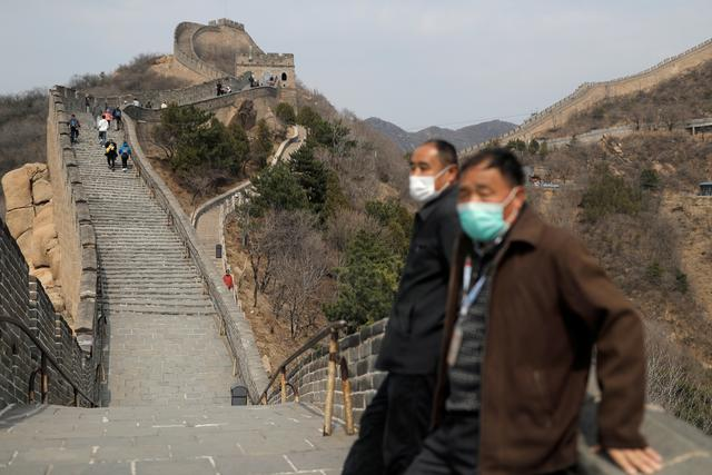 Men wearing protective masks stand as people hike along a section of the Great Wall in Badaling in Beijing, on its first day of re-opening after the scenic site's coronavirus related closure, China, March 24, 2020. REUTERS/Thomas Peter