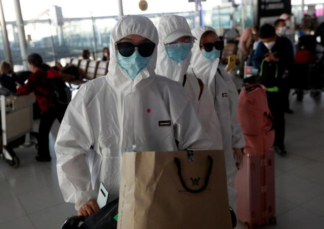 FILE PHOTO: Passengers in protective suits due to coronavirus disease (COVID-19) outbreak are seen before they check in at Suvarnabhumi Airport in Bangkok, Thailand March 24, 2020. REUTERS/Soe Zeya Tun