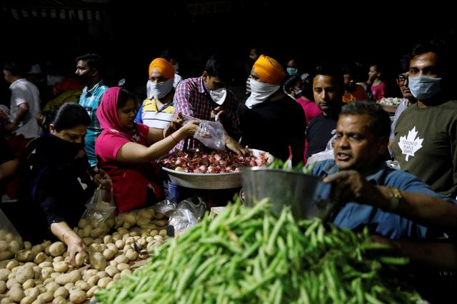 People buy vegetables at a market after India's Prime Minister Narendra Modi called for a nationwide lockdown starting midnight to limit the spreading of coronavirus disease (COVID-19), in New Delhi, India, March 24, 2020. REUTERS/Anushree Fadnavis