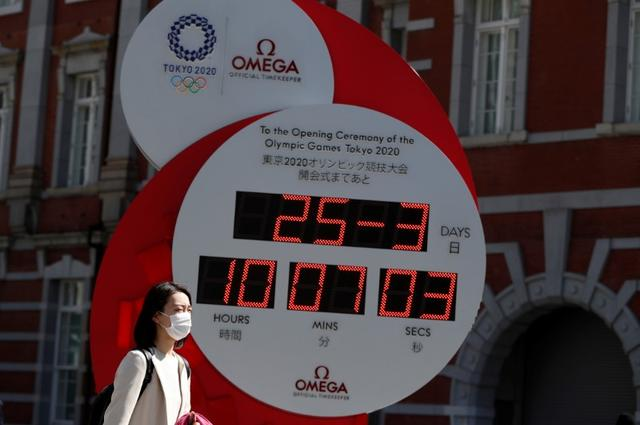 A woman wearing a protective face mask due to the outbreak of coronavirus disease (COVID 19) walks next to Omega clock, which was previously used as a countdown clock for the Tokyo 2020 Olympic Games and currently displaying current time and date, after the announcement of the games 'postponement to the summer of 2021, in Tokyo, Japan, March 25, 2020. REUTERS/Issei Kato