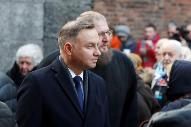 FILE PHOTO: Poland's President Andrzej Duda, seen in front of Director of the Auschwitz-Birkenau State Museum Piotr Cywinski, attends a wreath-laying ceremony at the death wall at the former Nazi German concentration and extermination camp Auschwitz in Oswiecim, Poland, January 27, 2020. REUTERS/Aleksandra Szmigiel/File Photo