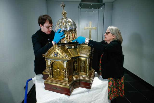 Restorer Luke Jonathan Koeppe and the director of the cathedral treasury Birgitta Falk present shrine with the relics of Saint Corona, the patron of epidemics, at the cathedral in Aachen, Germany, March 25, 2020 as the spread of the coronavirus disease (COVID-19) continues. REUTERS/Thilo Schmuelgen