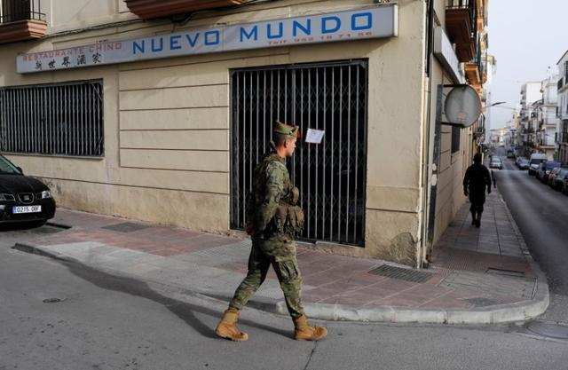 FILE PHOTO: Spanish legionnaires patrol an empty street during partial lockdown as part of a 15-day state of emergency to combat the coronavirus disease (COVID-19) outbreak, in downtown Ronda, southern Spain, March 18, 2020. REUTERS/Jon Nazca/File Photo