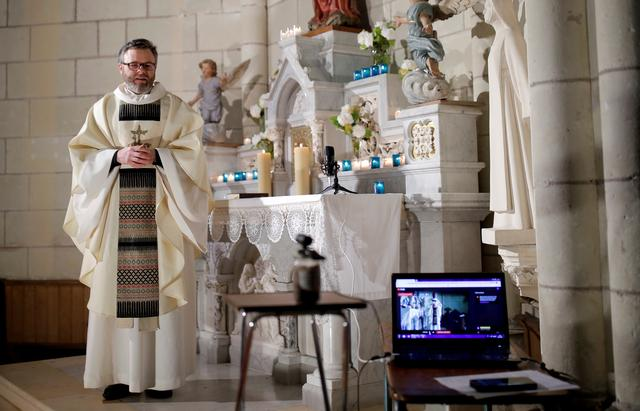 French priest Guillaume Le Floc'h conducts a mass streamed online on the feast of the Annunciation at the church in Carquefou near Nantes as a lockdown is imposed to slow the rate of the coronavirus disease (COVID-19) spread in France, March 25, 2020. REUTERS/Stephane Mahe