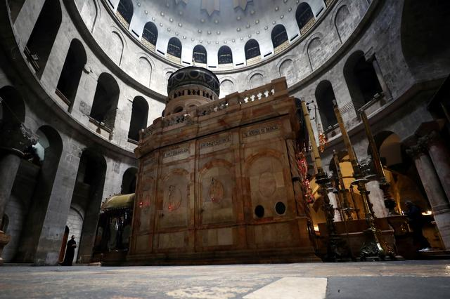 FILE PHOTO: A general view shows the structure housing the purported tomb of Jesus in the burial place, known as the Edicule, at the Church of the Holy Sepulchre, during a prayer session amid concerns over the spread of coronavirus disease (COVID-19), in Jerusalem's Old City March 22, 2020. REUTERS/Ammar Awad/FIle Photo