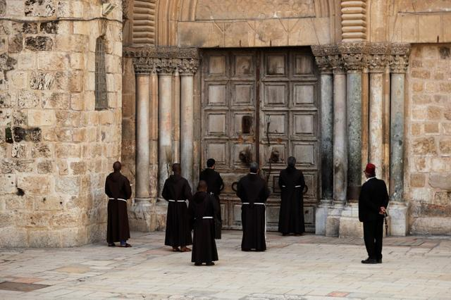 Roman Catholic monks pray in front of the locked door of Jerusalem's Church of the Holy Sepulchre amid coronavirus restrictions in the walled Old City March 27, 2020 REUTERS/ Ammar Awad