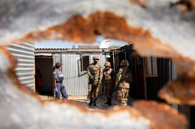 Soldiers and a police member are seen amongst shacks as authorities attempt to enforce a 21 day nationwide lockdown aimed at limiting the spread of coronavirus disease (COVID-19), in Khayelitsha township near Cape Town, South Africa, March 27, 2020. Reuters/Mike Hutchings