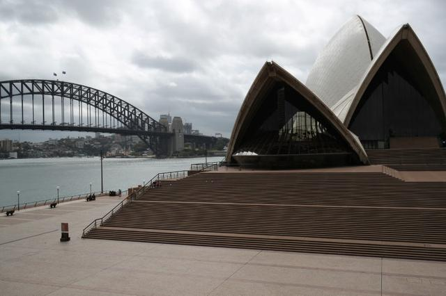 "People are seen on the nearly deserted steps of the Sydney Opera House, in the wake of New South Wales implementing measures shutting down non-essential businesses and moving toward harsh penalties to enforce self-isolation as the spread of coronavirus disease (COVID-19) reached what the state's premier calls a ""critical stage"" in Australia, March 26, 2020.  REUTERS/Loren Elliott"