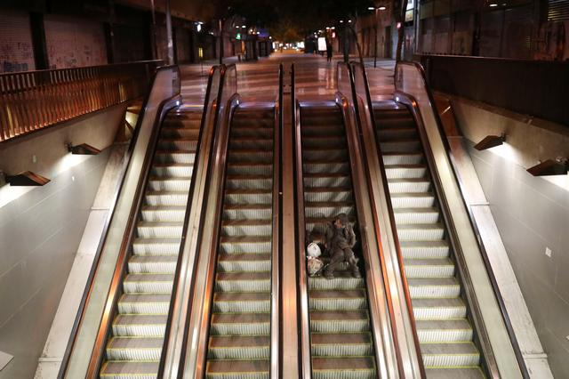 A homeless man sleeps on an escalator during a preventive quarantine following the outbreak of coronavirus disease (COVID-19), in Santiago, Chile, on March 27, 2020. REUTERS/Pablo Sanhueza