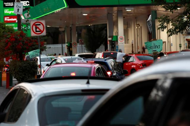 Cars line up to fill their tanks at a gas station offering the lowest price for a liter of gas in the city as the coronavirus disease (COVID-19) outbreak continues in Mexico City, Mexico, March 27, 2020. REUTERS/Henry Romero