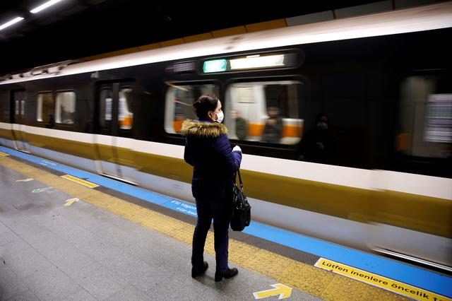 FILE PHOTO: A woman wearing a protective face mask waits for a train as the spread of the coronavirus disease (COVID-19) continues, Istanbul, Turkey, March 26, 2020. REUTERS/Umit Bektas/File Photo
