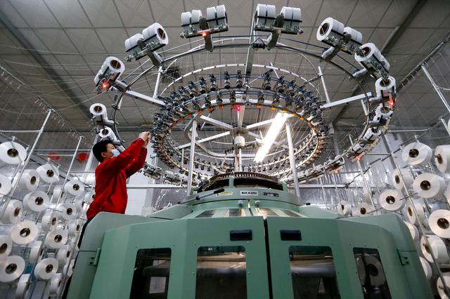 FILE PHOTO: A textile worker is seen on a fabric production line at a factory in Qingdao, Shandong province, China February 14, 2020. China Daily via REUTERS/File Photo