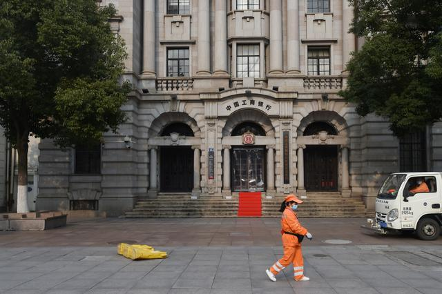 FILE PHOTO: A sanitation worker wearing a face mask walks past a branch of Industrial and Commercial Bank of China (ICBC) in Wuhan, the epicentre of the novel coronavirus outbreak, Hubei province, China February 25, 2020. REUTERS/Stringer