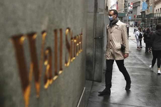 A man wears a protective mask as he walks on Wall Street during the coronavirus outbreak in New York City, New York, U.S., March 13, 2020. REUTERS/Lucas Jackson
