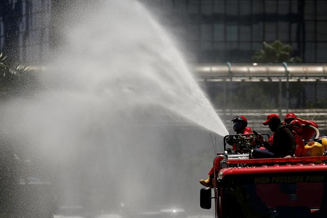 Firefighters spray disinfectant using high pressure pump truck to prevent the spread of coronavirus disease (COVID-19), on the main road in Jakarta, Indonesia, March 31, 2020. REUTERS/Willy Kurniawan