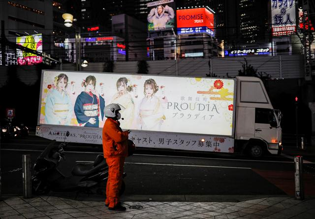 A biker wearing a protective face mask, following the outbreak of the coronavirus disease (COVID-19), stands on the street as a truck with advertisements of a night club runs past at Shinjuku district in Tokyo, Japan March 31, 2020. REUTERS/Issei Kato