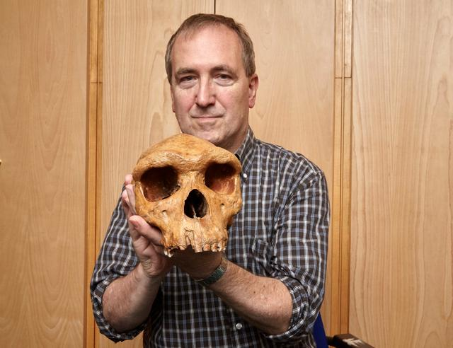 The Natural History Museum's Professor Chris Stringer is seen holding the Broken Hill skull, Homo heidelbergensis, a fossil of an extinct human species found in Zambia in 1921 in this undated image provided to Reuters March 31, 2020.  Kevin Webb/NHM Image Resources/The Trustees of the Natural History Museum in London/Handout via REUTERS.