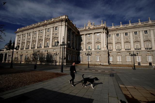 A man walks his dog next to the Royal Palace during lockdown, amid the coronavirus disease (COVID-19) outbreak, in Madrid, Spain April 5, 2020. REUTERS/Juan Medina