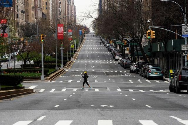 A woman crosses the empty of street Park Avenue in Manhattan as the outbreak of coronavirus disease (COVID-19) continues in New York, U.S., April 5, 2020. REUTERS / Eduardo Munoz