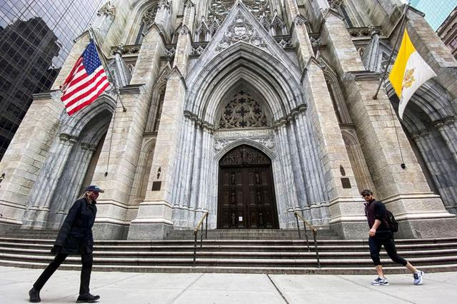 People walk in front of the St. Patrick Cathedral shuttered to believers during Palm Sunday as the outbreak of coronavirus disease (COVID-19) continues in New York, U.S., April 5, 2020. REUTERS / Eduardo Munoz