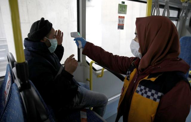 The medic checks the temperature of a passenger in a bus on a highway near Istanbul after the government decided to shut down the borders of  31 cities for all vehicles excluding transit passage for essential supplies, as the spread of coronavirus disease (COVID-19) continues, at the outskirts of Istanbul, Turkey April 4, 2020. REUTERS/Umit Bektas