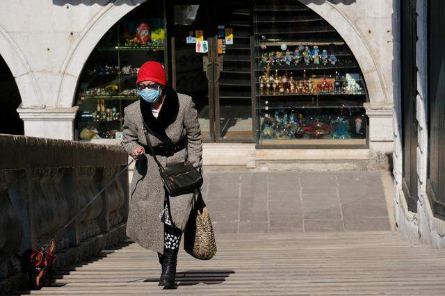 A woman wearing a protective mask walks on the Rialto Bridge on Palm Sunday, following the coronavirus disease (COVID-19) outbreak in Venice, Italy, April 5, 2020. REUTERS/Manuel Silvestri