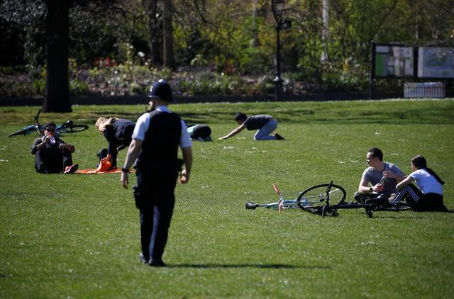 People sit on the grass as police patrol in St James' Park, as the spread of the coronavirus disease (COVID-19) continues, London, Britain, April 5, 2020. REUTERS/Henry Nicholls