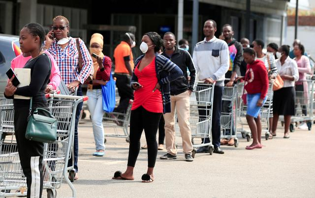 FILE PHOTO: People queue to shop ahead of a nationwide 21-day lockdown called by the government to limit the spread of coronavirus disease (COVID-19) in Harare, Zimbabwe, March 28, 2020. REUTERS/Philimon Bulawayo/File Photo