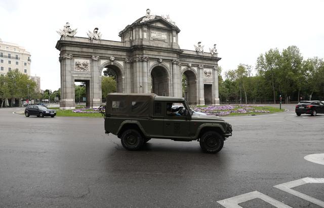 A Spanish Army vehicle patrols past the almost empty landmark Alcala Gate, amid the coronavirus disease (COVID-19) outbreak in Madrid, Spain, April 9, 2020. REUTERS/Sergio Perez