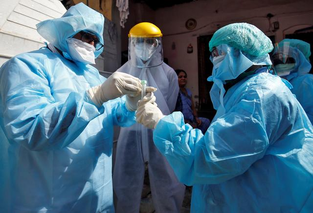 Doctors wearing protective gear seal a vial after taking a swab from a woman to test for coronavirus disease (COVID-19) at a residential area in Ahmedabad, India, April 9, 2020. REUTERS/Amit Dave