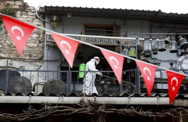 FILE PHOTO: A worker in a protective suit sprays disinfectant at Grand Bazaar, known as the Covered Bazaar, to prevent the spread of coronavirus disease (COVID-19), in Istanbul, Turkey, March 25, 2020. REUTERS/Umit Bektas/File Photo