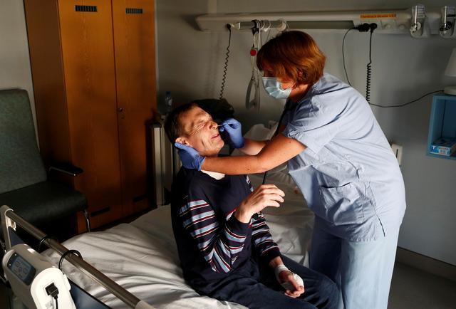 Belgian doctor Elisabeth Lenoir takes a swab from Rudi Delfosse, a 53-year-old homeless man, to test for coronavirus disease (COVID-19) at the palliative unit of a hospital near Arlon, Belgium April 7, 2020.  REUTERS/Francois Lenoir