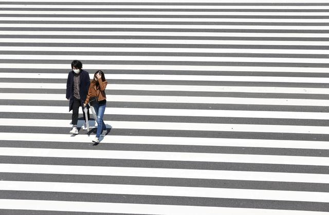 People walk on the crosswalk, downtown, which has less than usual passersby after the state of emergency was announced, following the coronavirus disease (COVID-19) outbreak, in Shinjuku City, Tokyo, Japan, in this photo taken by Kyodo April 11, 2020. Mandatory credit Kyodo via REUTERS