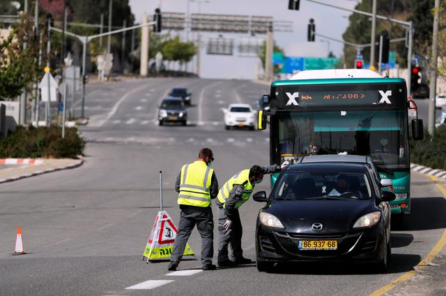 Israeli police check a driver in a car on a roadblock in a main road in Jerusalem as they try to contain the spread of the coronavirus  disease (COVID-19) from the densely populated neighborhoods where the infection rate is high, April 12, 2020 REUTERS/ Ammar Awad