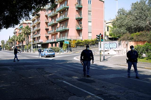 FILE PHOTO: Police officers stand on a street to check people amid spread of the coronavirus disease (COVID-19), in Catania, Italy April 12, 2020. REUTERS/Antonio Parrinello