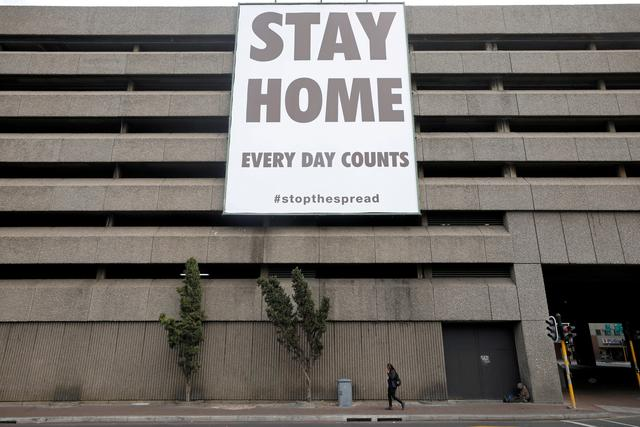 FILE PHOTO: A man walks beneath a billboard during the 21-day nationwide lockdown aimed at limiting the spread of coronavirus disease (COVID-19) in central Cape Town, South Africa, April 6, 2020. REUTERS/Mike Hutchings