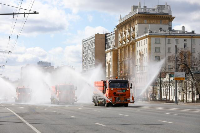 Vehicles drive near the U.S. embassy and spray disinfectant while sanitizing a road to prevent the spread of the coronavirus disease (COVID-19) in Moscow, Russia April 12, 2020. Andrey Nikerichev/Moscow News Agency/Handout via REUTERS