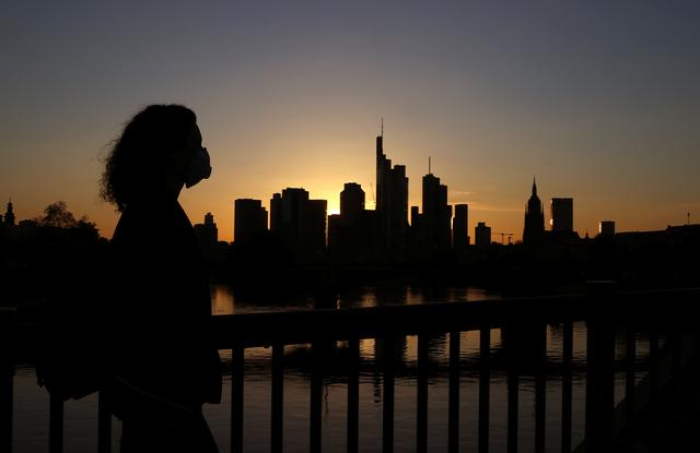 A woman wearing a protective mask crosses a bridge in front of the skyline in Frankfurt, Germany, April 14, 2020, as the spread of the coronavirus disease (COVID-19) continues.   REUTERS/Kai Pfaffenbach