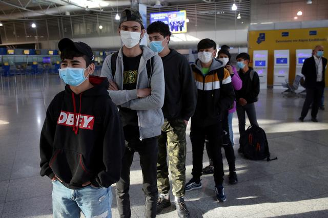 A group of unaccompanied children from overcrowded migrant camps who will be transferred to Luxembourg, wear protective face masks as a precaution against the spread of coronavirus disease (COVID-19) as they wait to board their flight at the Athens International Airport, Greece, April 15, 2020. Orestis Panagiotou/Pool via REUTERS
