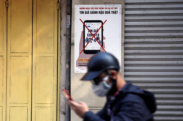 FILE PHOTO: A man uses a smartphone as he walks past a poster warning against spreading 'fake news' on the coronavirus in Hanoi, Vietnam April 14, 2020.  REUTERS/Kham
