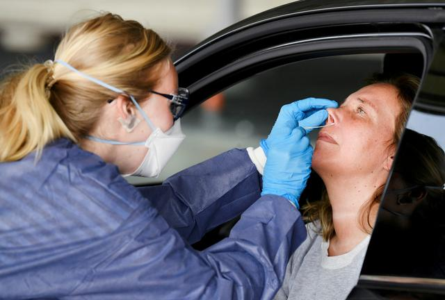 FILE PHOTO: A member of medical staff takes coronavirus test samples of a woman during drive-thru coronavirus disease (COVID-19) testing, on a converted ice rink, in Alkmaar, Netherlands April 8, 2020.  REUTERS/Piroschka van de Wouw