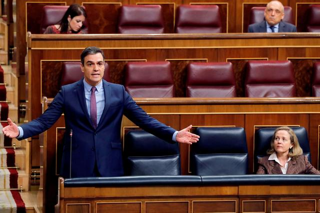 Spanish Prime Minister Pedro Sanchez answers questions as he keeps social distance from Deputy Prime Minister and Economic Affairs Minister Nadia Calvino during a control session on coronavirus disease (COVID-19) at the Parliament in Madrid, Spain, April 15, 2020. Ballesteros/Pool via REUTERS