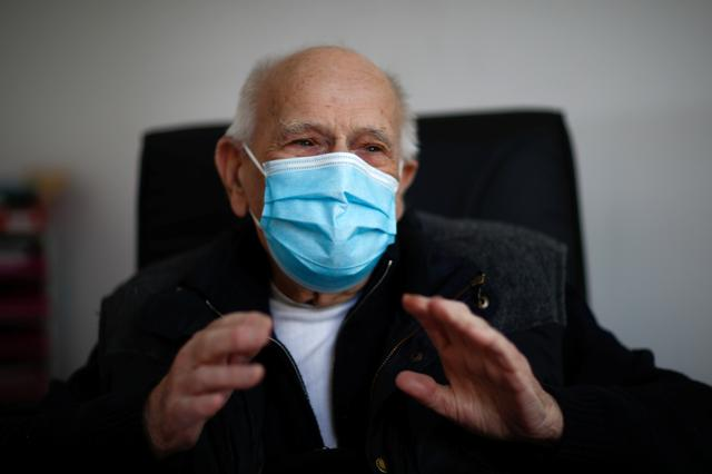 French doctor Christian Chenay, 98 year-old, wearing a protective face mask, sits in his consulting room at the doctor's office in Chevilly-Larue near Paris as the spread of the coronavirus disease (COVID-19) continues in France April 14, 2020. REUTERS/Gonzalo Fuentes